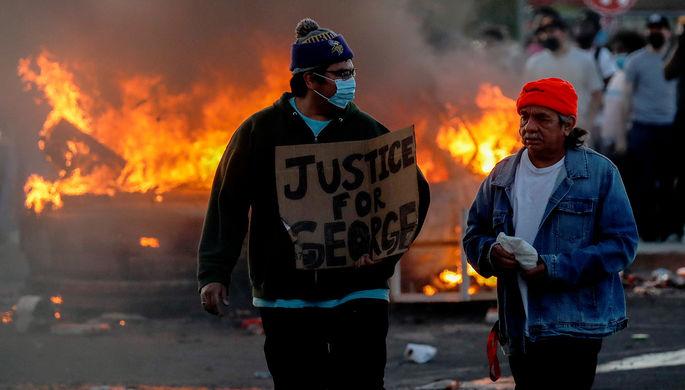 Протестующие около горящего автомобиля на парковке супермаркета во время беспорядков в Миннеаполисе, 28 мая 2020 года