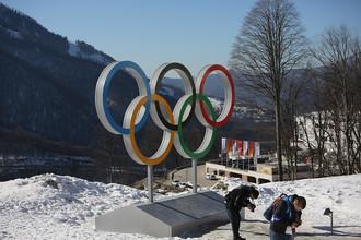 Корреспонденты пытаются разглядеть на ярком солнце отснятые фотографии олимпийских колец
