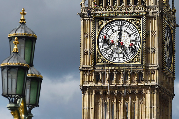 Верхолазы спускаются на одну из сторон Биг-Бена в Лондоне для очистки и полировки циферблата часов