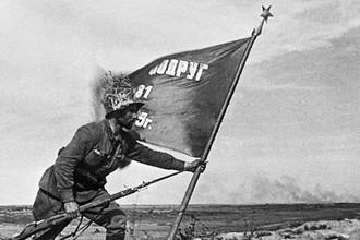 Заместитель командира взвода Г. П. Доля со знаменем на сопке Ремизова во время боев на реке Халхин-Гол, 1939 год