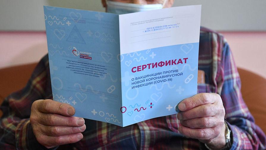 Мужчина держит в руках сертификат о вакцинации против коронавирусной инфекции (COVID-19)