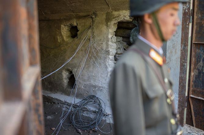 Военнослужащий у входа в шахту для ядерных испытаний №4 на ядерном полигоне Пхунгери на севере КНДР, 24 мая 2018 года