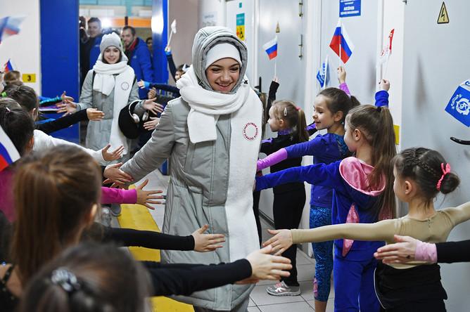 Фигуристки Алина Загитова и Евгения Медведева (в центре слева направо) во время торжественных проводов на Олимпиаду