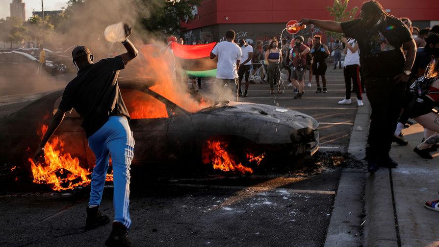 Горящий автомобиль на парковке супермаркета во время беспорядков в Миннеаполисе, 28 мая 2020 года