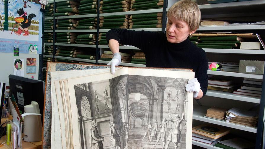Сотрудник Центральной универсальной научной библиотеки им. Некрасова демонстрирует старинную редкую книгу