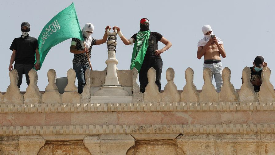 Жители Палестины держат флаг ХАМАС в районе мечети «Аль-Акса» на Храмовой горе в Иерусалиме, 10 мая 2021 года