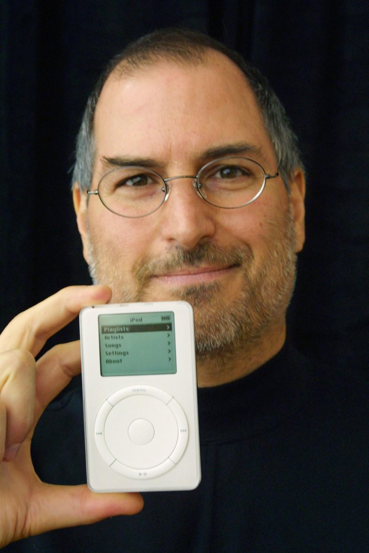 <b>iPod (2001)</b><br><br> Специально к выходу первого портативного плеера iPod Стив Джобс придумал слоган «1000 songs in your pocket» [1000 песен у Вас в кармане], что на те времена было очень внушительным количеством. iPod стал настоящей сенсацией в мире MP3-плееров и в дальнейшем получил несколько вариаций — Mini, Nano, Shuffle и Touch, каждая из которых имела свой уникальный дизайн. На фото Джобс во время презентации iPod в Купертино в 2001 году