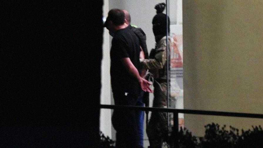 Вооруженный мужчина вместе с тремя заложниками покидает отделение Банка Грузии в Зугдиди, 21 октября 2020 года