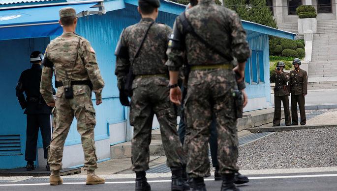 Северокорейские и южнокорейские солдаты во время посещения деревни Пханмунджом на границе КНДР и...