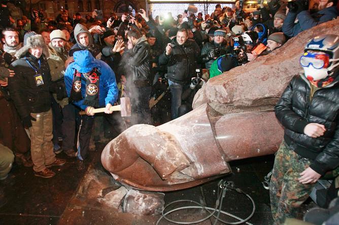 Демонстранты разбивают рухнувший памятник Ленину кувалдами