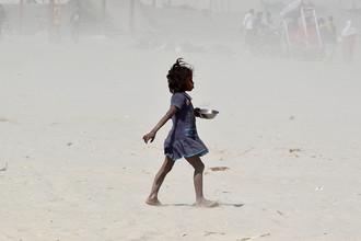 Девочка во время песчаной бури на берегу реки Ганг в индийском Аллахабаде, 24 февраля 2017 года