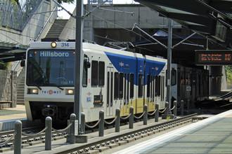 Поезд легкого метро прибывает на станцию — пересадочный узел Бивертон-Сансет в Бивертоне, штат Орегон, США