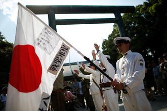 Солдаты в форме императорской армии поднимают флаги Японии во время мемориальной церемонии в храме Ясукуни в Токио, 15 августа 2015 года