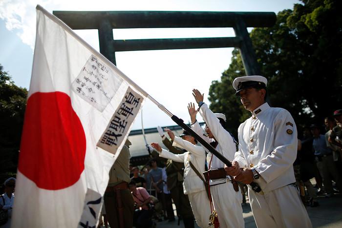 Солдаты в форме императорской армии поднимают флаги Японии во время мемориальной церемонии в храме...