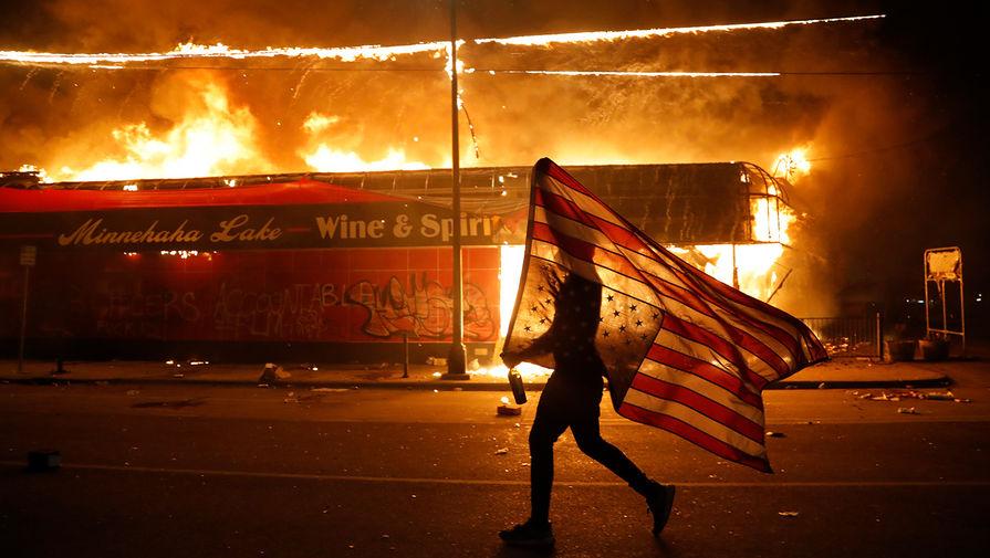 Человек с перевернутым флагом США и горящее здание во время беспорядков в Миннеаполисе, 28 мая 2020 года