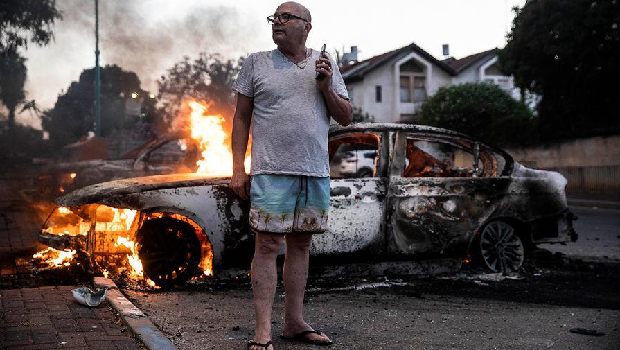 Джейкоб Симона стоит у своей горящей машины во время столкновений между арабскими и еврейскими жителями в смешанном израильском городе Лод (Израиль), 11 мая 2021 года