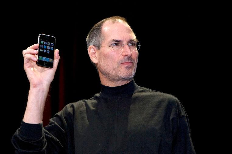 <b>iPhone (2007)</b><br><br> Наверное, самый культовый продукт Apple, который до сих пор является визитной карточкой компании. Устройство с экраном с диагональю 3,5 дюйма на базе операционной системы iOS навсегда изменило рынок мобильных устройств и продолжает оказывать на него заметное влияние и по сей день. На фото Стив Джобс во время презентации первого &laquo;айфона&raquo; в 2007 году