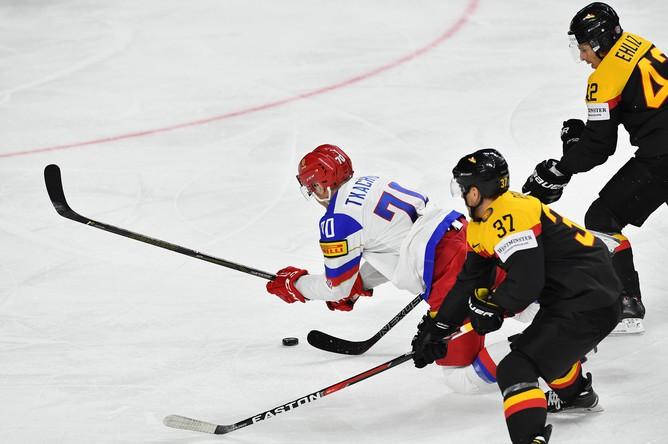Игрок сборной России Владимир Ткачев уходит от Патрика Раймера и Ясина Эхлица в матче группового этапа чемпионата мира по хоккею 2017 между сборными командами Германии и России