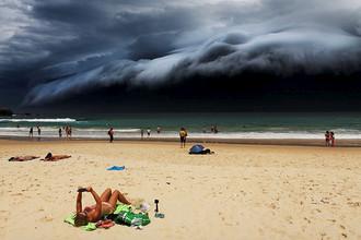 Загорающая девушка не обращает внимания на зловещее облако, которое приближается к пляжу Бонди-Бич в Австралии