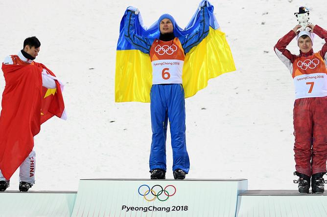 Цзя Цоньянь (Китай), занявший второе место, Александр Абраменко (Украина), занявший первое место и Илья Буров (Россия), занявший третье место в финале лыжной акробатики на соревнованиях по фристайлу среди мужчин на XXIII зимних Олимпийских играх в Пхенчхане, на цветочной церемонии