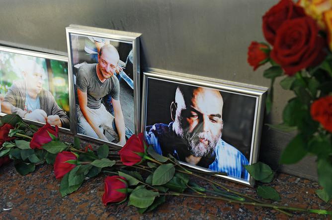 Цветы у фотографий погибших в ЦАР журналистов: Орхана Джемаля, Кирилла Радченко и Александра Расторгуева (справа налево) возле Дома журналистов в Москве, 1 августа 2018 года