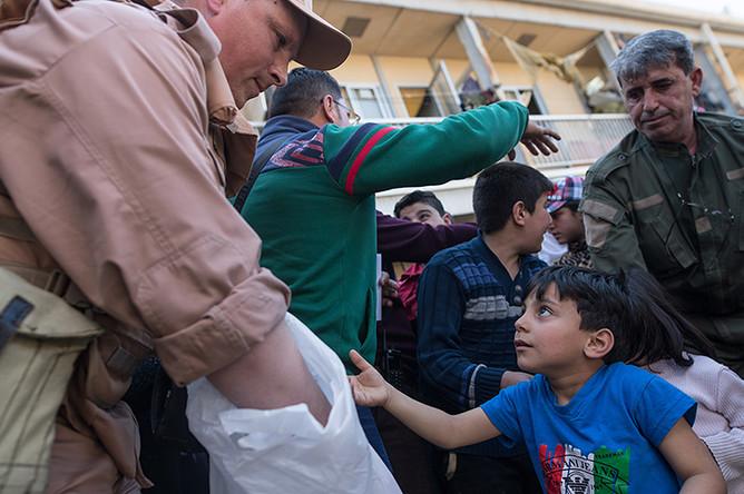 Сотрудник Координационного центра по примирению враждующих сторон в Сирии во время раздачи гуманитарной помощи от России в лагере внутренне перемещенных лиц в бывшей гостинице вагоностроительного завода у города Хамы