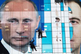 Плакат с изображением президента России Владимира Путина и премьер-министра Дмитрия Медведева на одном из зданий в Краснодаре