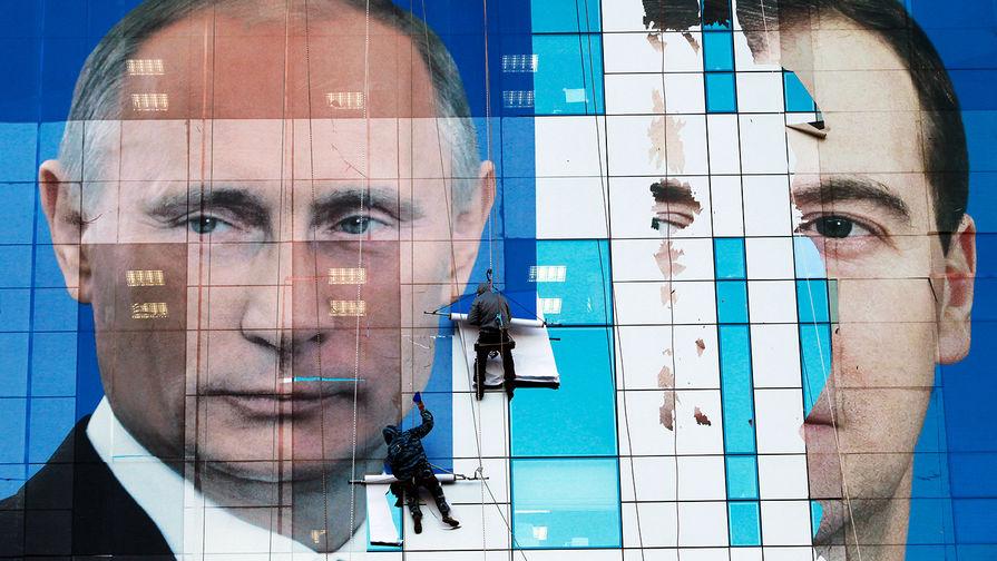 Плакат с изображением президента России Владимира Путина и премьер-министра Дмитрия Медведева на...
