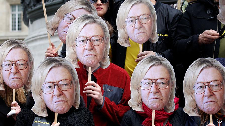 Активисты в масках с изображением французского политика Жана-Мари Ле Пен с волосами его дочери Марин...