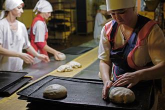 Работницы краснодонского хлебозавода «Золотой урожай» на линии по производству заготовок для булок в одном из цехов предприятия в городе Краснодоне Луганской области