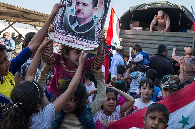 Дети во время раздачи гуманитарной помощи от России в лагере внутренне перемещенных лиц в бывшей гостинице вагоностроительного завода у города Хама