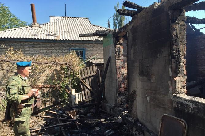 Ополченец осматривает дом, пострадавший в результате обстрела украинскими силовиками города Горловки Донецкой области
