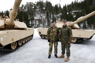 Норвежский и американский военные на фоне танков Abrams M1A1 во время февральских учений Cold Response в Трёнделаге