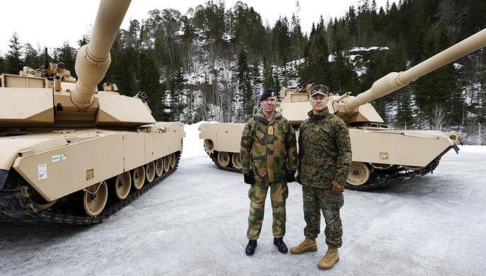 Норвежский и американский военные на фоне танков Abrams M1A1 во время февральских учений Cold...