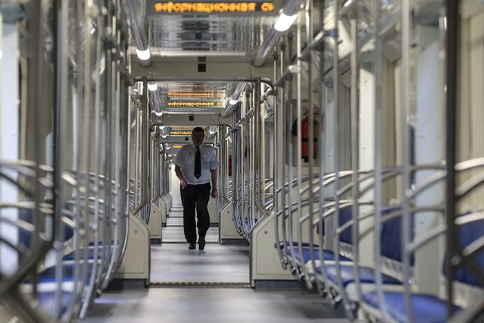 Пассажиры в вагоне поезда серии 81-760А со сквозным проходом по всей длине состава во время...