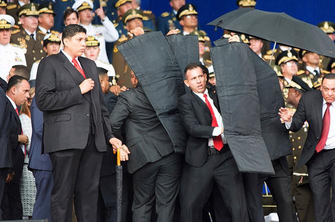 Охранники закрывают щитами президента Венесуэлы Николаса Мадуро