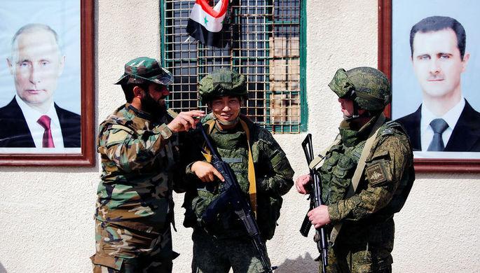 Российские и сирийский военнослужащие на фоне портретов президентов Владимира Путина и Башара Асада...