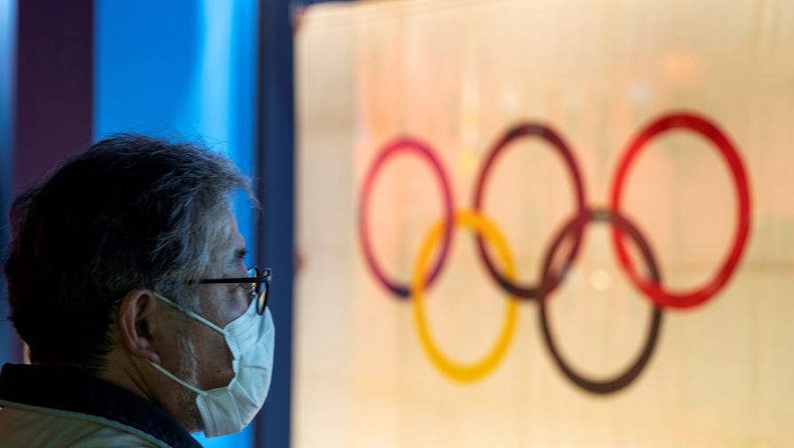 Мужчина в защитной маске смотрит на символ Олимпийских игр в Токио