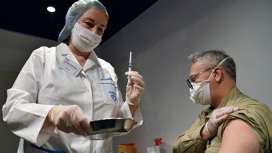Мужчине делают прививку от коронавируса в пункте вакцинации в ГУМе в Москве, 18 января 2021 года