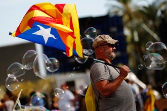 Мужчина с флагом Каталонии во время митинга в Барселоне, 10 октября 2017 года