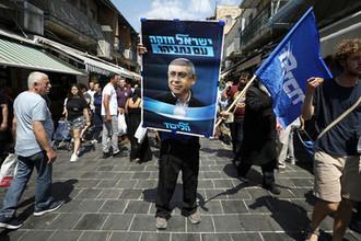 Сторонник партии «Ликуд» с предвыборным плакатом с изображением израильского премьера Биньямина Нетаньяху на рынке в Иерусалиме, 13 сентября 2019 года