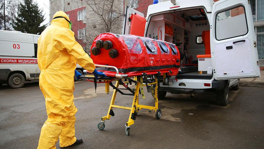Врач бригады скорой помощи в защитном костюме загружает бокс для перевозки зараженных коронавирусом в машину