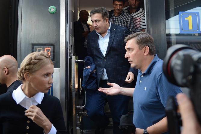 Экс-президент Грузии, бывший губернатор Одесской области Михаил Саакашвили выходит из вагона поезда на железнодорожном вокзале в польском Пшемышле. Слева- лидер всеукраинского объединения «Батькивщина» Юлия Тимошенко.
