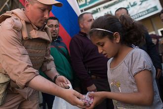 Сотрудник Координационного центра по примирению враждующих сторон в Сирии во время раздачи гуманитарной помощи от России в лагере внутренне перемещенных лиц в бывшей гостинице вагоностроительного завода у города Хама