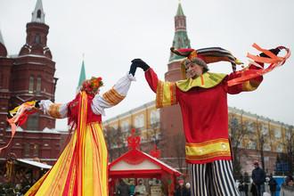 Участники анимационной программы, одетые в праздничные костюмы, во время открытия фестиваля «Московская Масленица» на Манежной площади