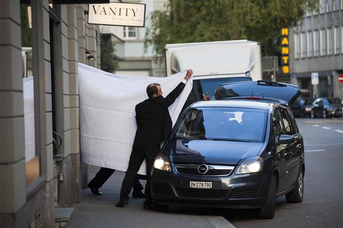 Полицейские проводили задержанных в припаркованные около черного входа отеля автомобили, закрыв их лица взятыми у сотрудников Baur au Lac простынями