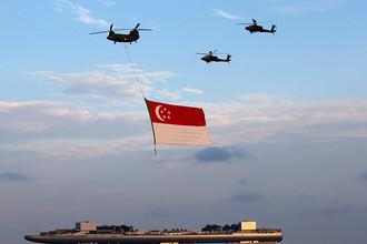 Вертолеты ВВС Сингапура пролетают с национальным флагом над заливом Марина-Бэй в честь 50-летней годовщины независимости Сингапура