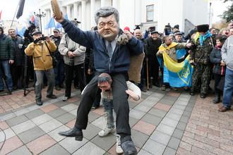 Участник протестного митинга перед зданием Верховной рады в центре Киева в маске президента Украины Петра Порошенко, 22 октября 2017 года