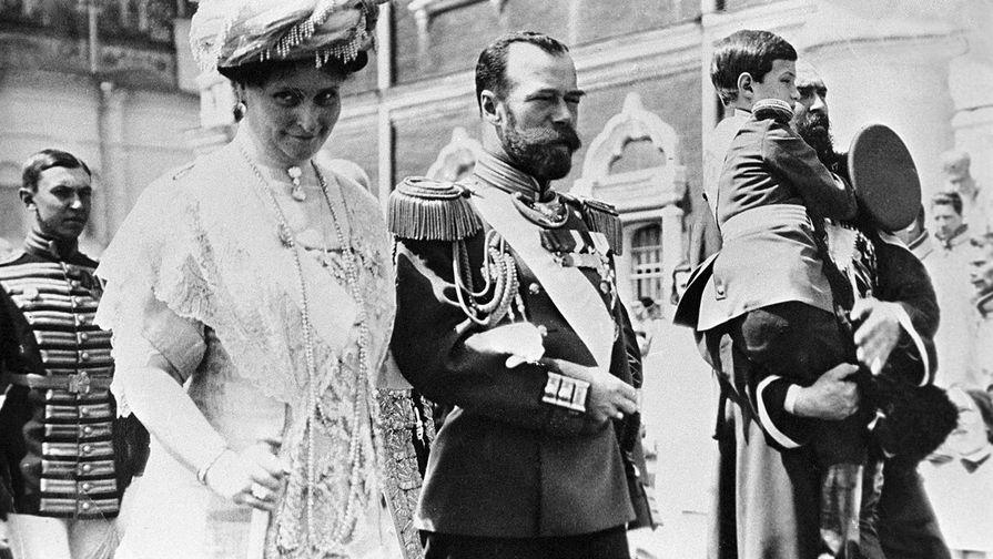 Российский император Николай II (в центре), императрица Александра Федоровна (слева) и цесаревич Алексей (на руках справа) в Кремле