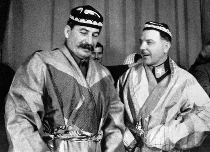 Иосиф Сталин и Климент Ворошилов в национальных костюмах от делегатов — участников совещания передовых колхозников Туркмении и Таджикистана, 1935 год